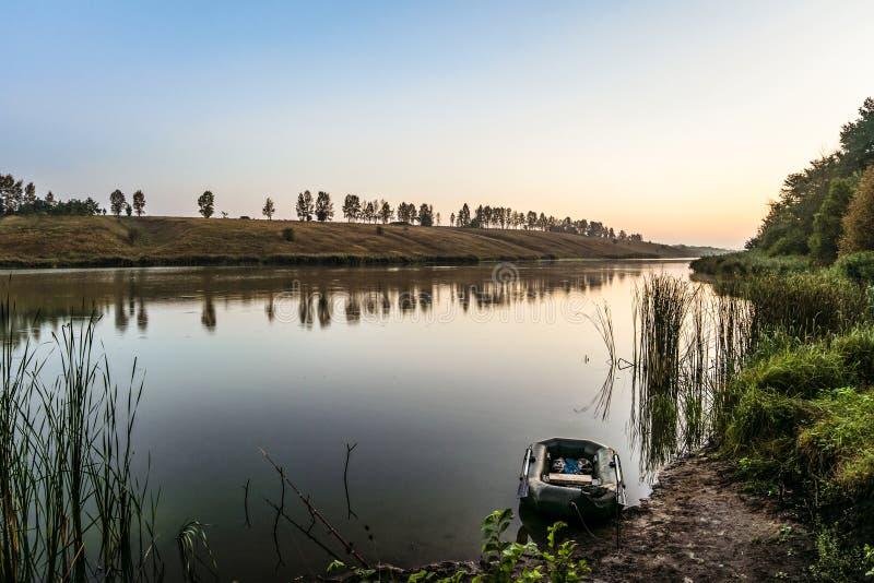 Vastgelegde visserij opblaasbare rubberboot en een hengel dichtbij de kust van het meer De zomer vroege ochtend en zonsopgang stock foto