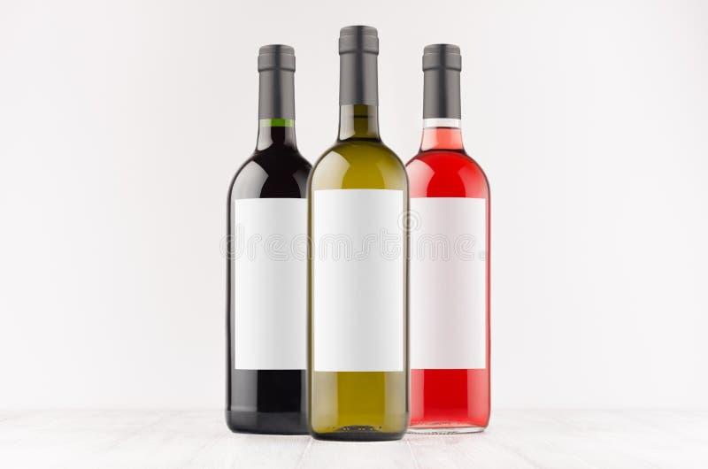 Vastgestelde rode wijnflessen -, groen, zwart met lege witte omhoog etiketten op witte houten raad, spot royalty-vrije stock fotografie