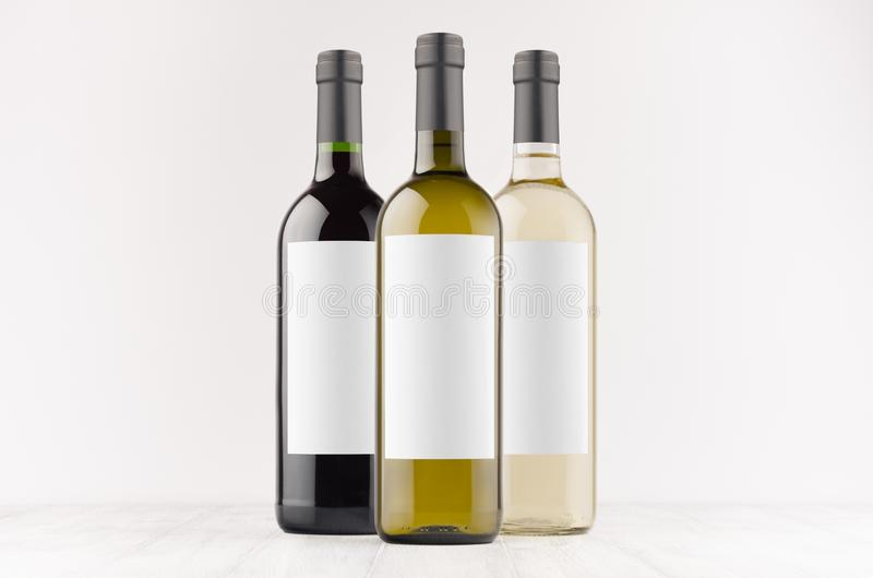 Vastgestelde transparante wijnflessen -, groen, zwart met lege witte omhoog etiketten op witte houten raad, spot stock foto