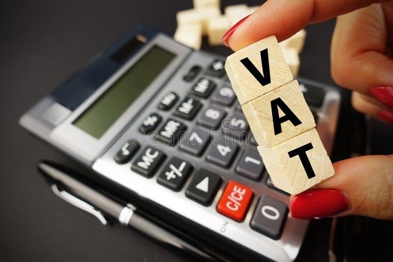 VAT演算概念用举行在木立方体的妇女手大桶词在黑暗的背景的计算器键盘上 库存照片