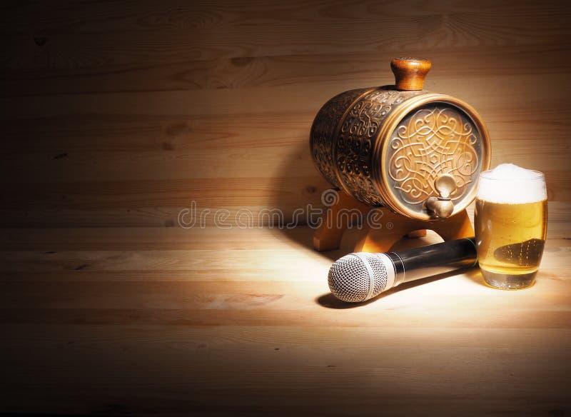 Vat en glas bier, microfoon op houten achtergrond conceptenkaraoke stock afbeeldingen
