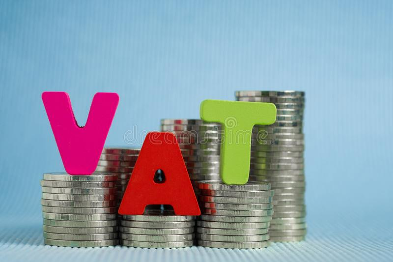 VAT (Value Added Tax) concept. Word VAT alphabet made from wood. With stack of coin, business and financial concept idea royalty free stock images