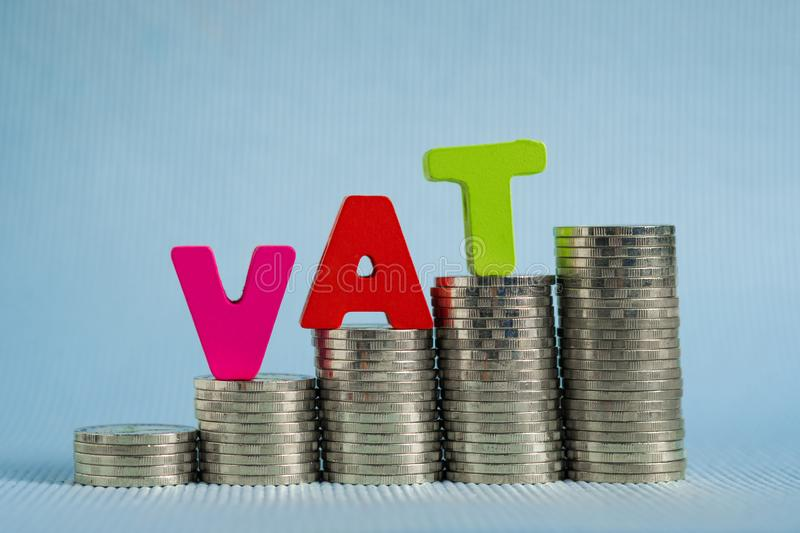 VAT (Value Added Tax) concept. Word VAT alphabet made from wood. With stack of coin, business and financial concept idea royalty free stock photo
