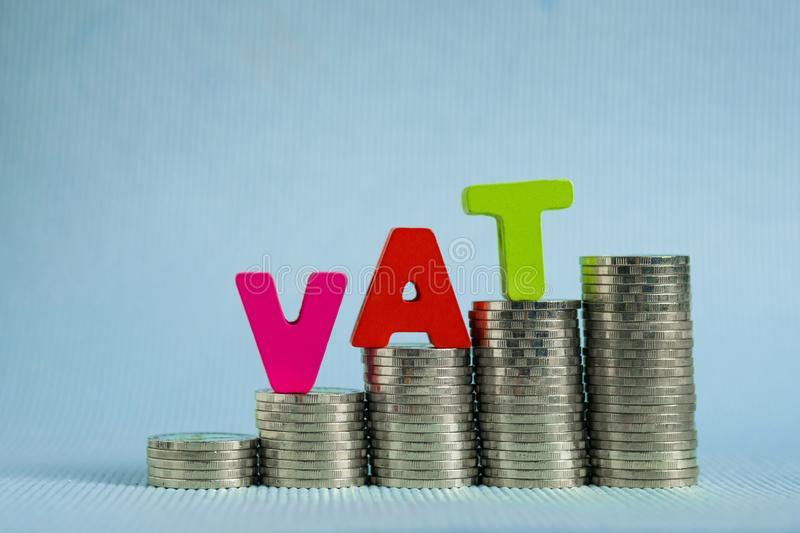 VAT (Value Added Tax) concept. Word VAT alphabet made from wood. With stack of coin, business and financial concept idea stock photography