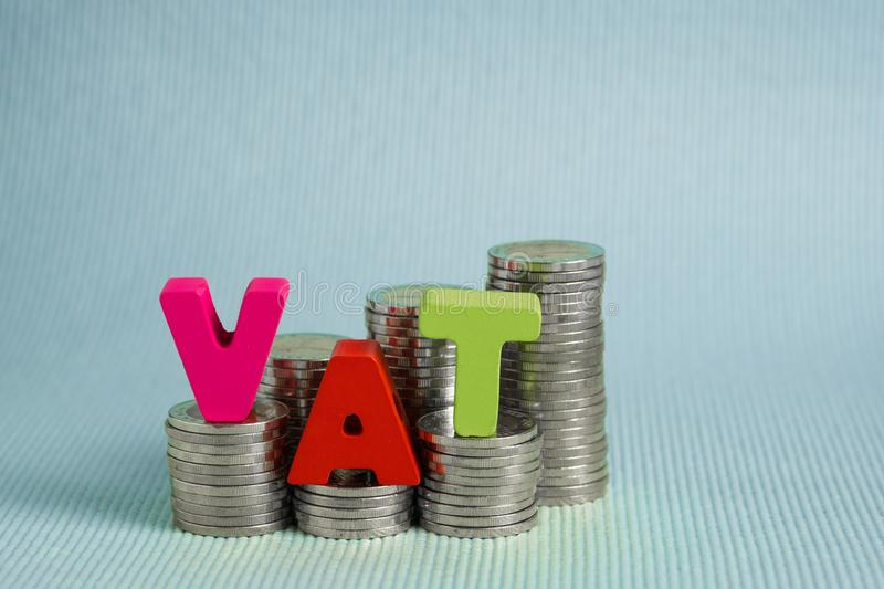 VAT Value Added Tax concept. Word VAT alphabet made from wood. With stack of coin, business and financial concept idea royalty free stock photos