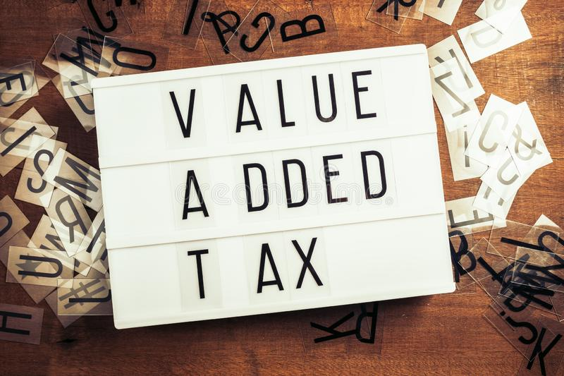 VAT or Value Added Tax on Lightbox. Vat or Value Added Tax on the lightbox with plastic alphabets scattered on wood background royalty free stock photo