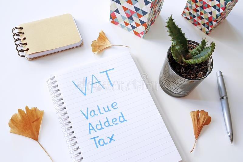 VAT Value Added Tax written in notebook. On white table royalty free stock photos