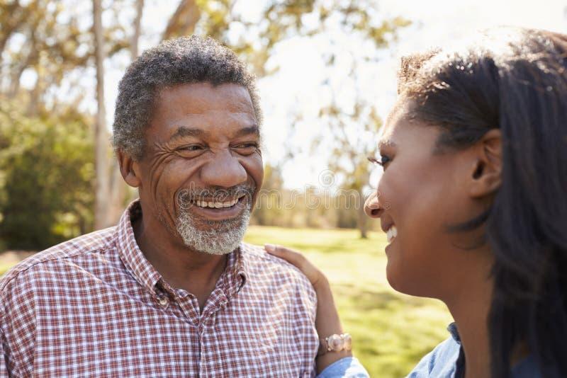 Vater And Adult Daughter, das zusammen im Park spricht lizenzfreie stockfotografie