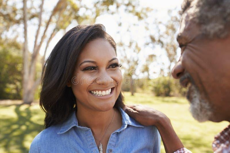 Vater And Adult Daughter, das zusammen im Park spricht lizenzfreie stockfotos
