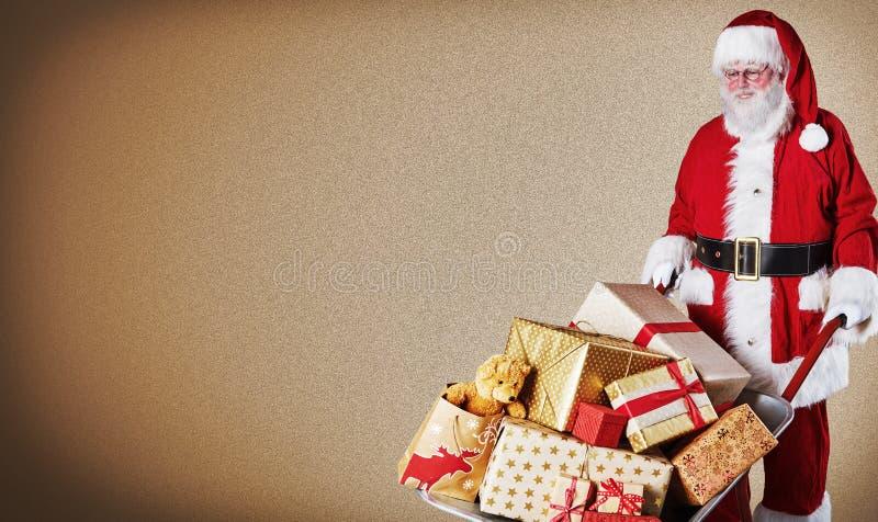 Vater Christmas, der eine Schubkarre von bunten eingewickelten Geschenken über einem braunen Steigungshintergrund mit Kopienraum  stockbilder