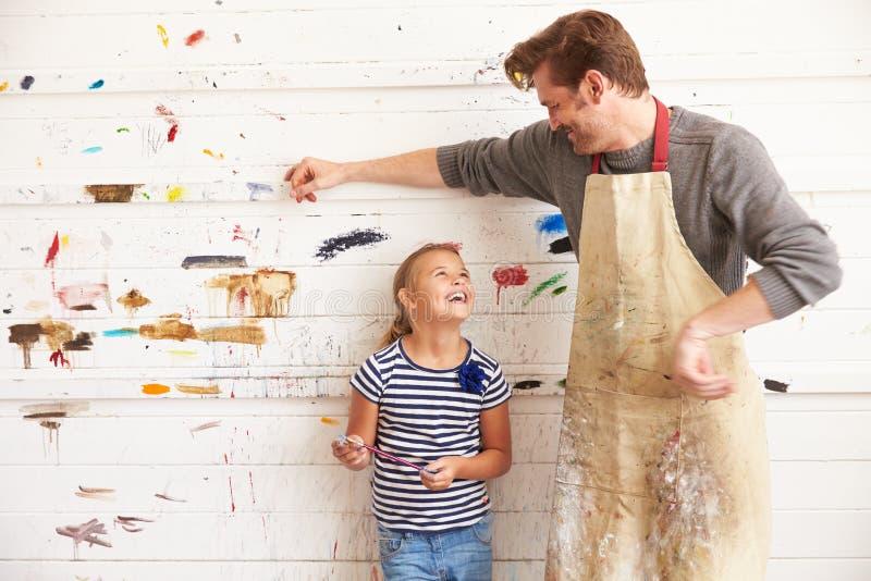 Vater-And Daughter Against-Farbe bedeckte Wand in Art Studio lizenzfreie stockfotografie