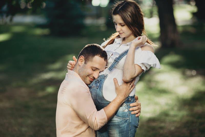 Vater, der auf das Baby umzieht innerhalb des Bauches hört stockfotografie