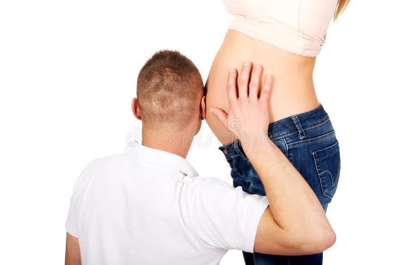 Vater, der auf den schwangeren Bauch der Mutter hört stockfotos