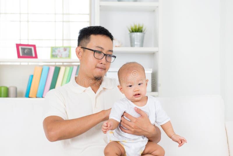 Vater, der Baby nach Mahlzeit rülpst stockbild