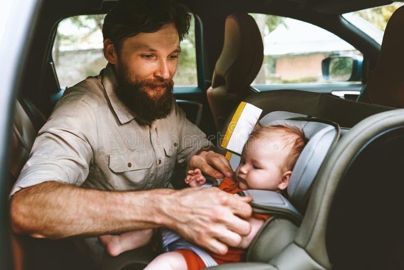 Vater, der Baby in Sicherheitsautositzgl?ckliche Familie einsetzt lizenzfreies stockbild
