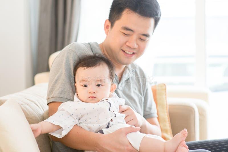 Vater, der das Baby sitzt auf Sofa hält stockfotografie