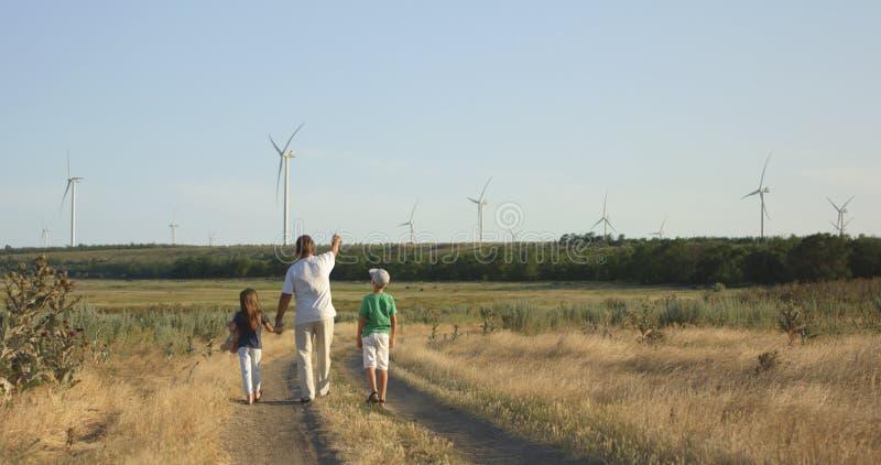 Vater, der den Kindern Windmühlen zeigt lizenzfreie stockfotos