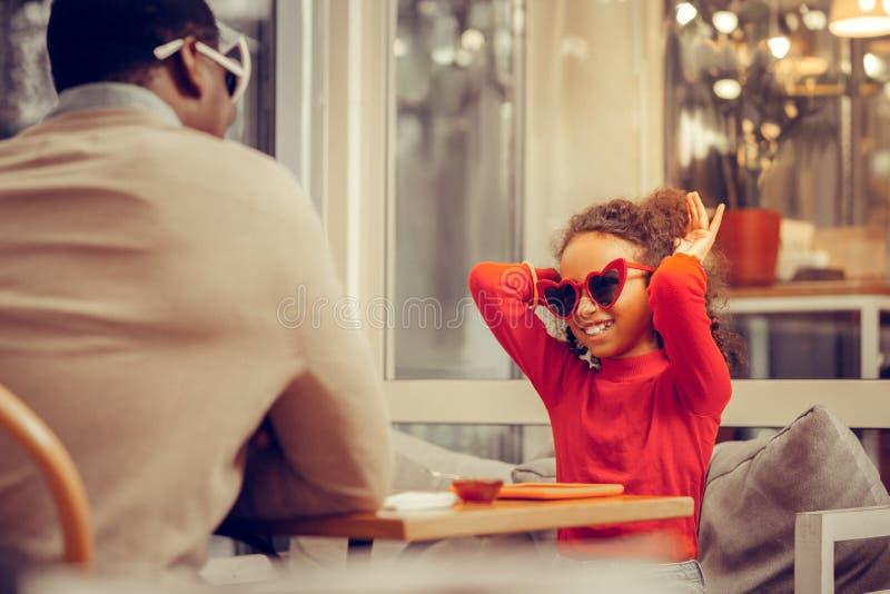 Vater, der die beige Strickjacke unterhält seine nette kleine Prinzessin trägt stockfotos