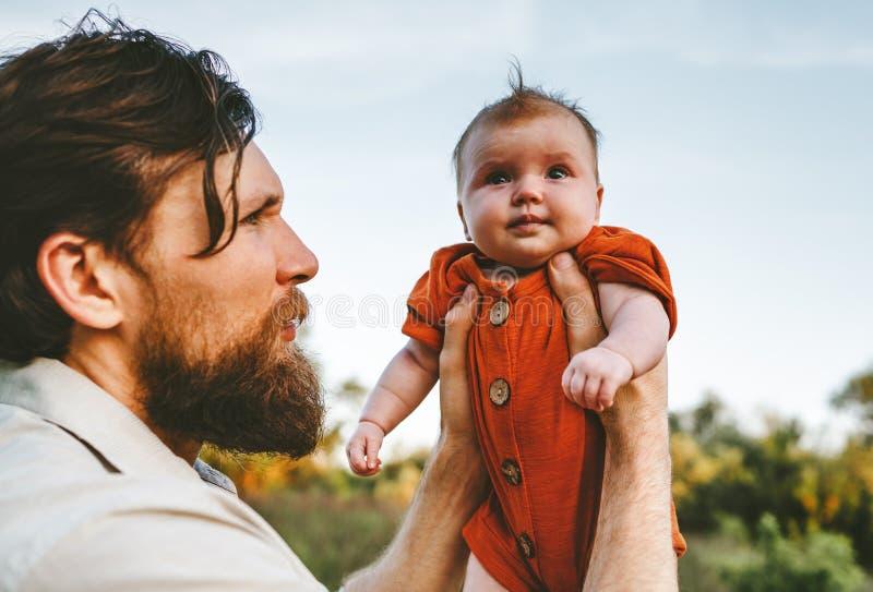 Vater, der Familienlebensstil des S?uglingsbabys im Freien h?lt stockbild