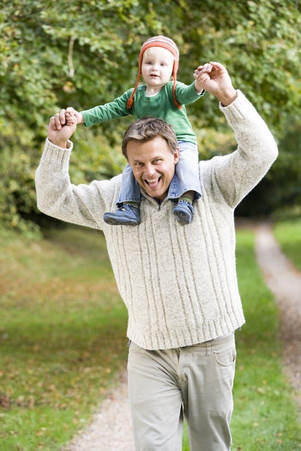 Vater, der junge Sohnfahrt auf Schultern gibt stockbild