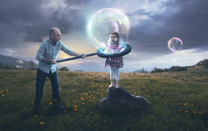Vater, der Kind in eine Blase einsetzt stockfotos