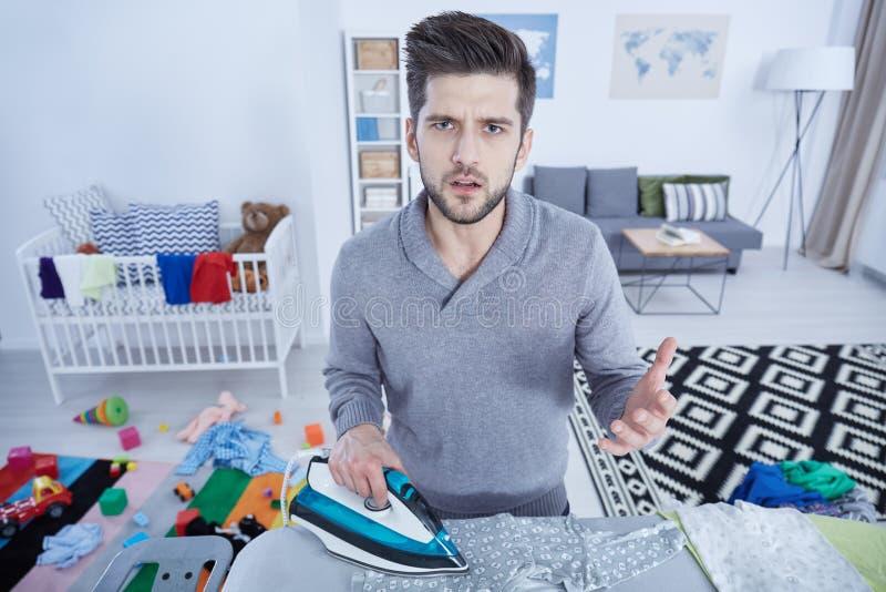 Vater, der in Kind-` s Raum bügelt stockfoto