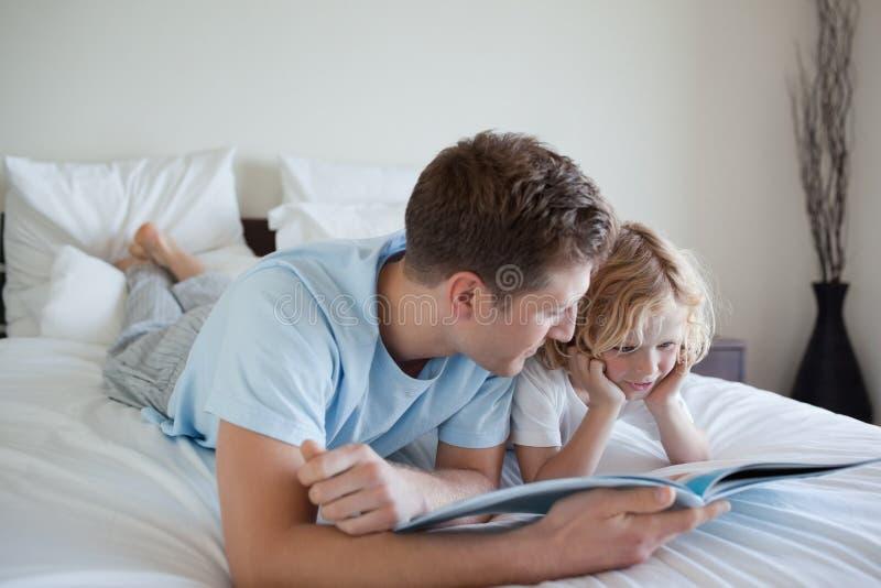 Vater, der Leseübungen mit seinem Sohn tut stockbilder