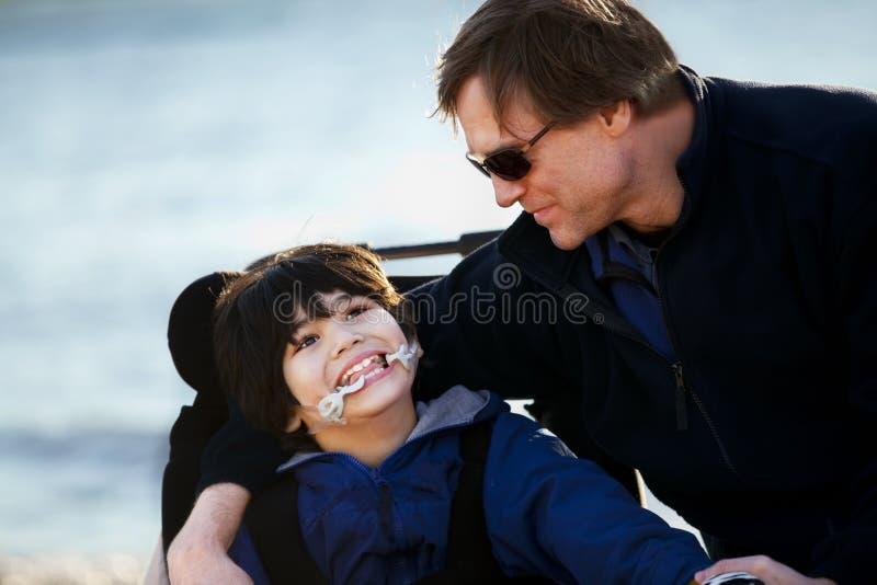 Vater, der mit behindertem Sohn entlang Seeufer sitzt lizenzfreies stockbild