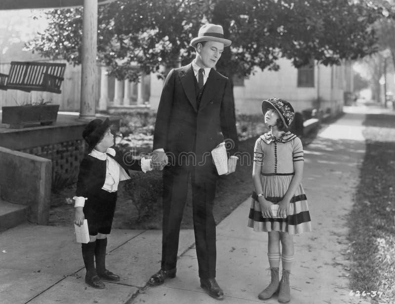 Vater, der mit der zwei Kinderaußenseite spricht (alle dargestellten Personen sind nicht längeres lebendes und kein Zustand exist stockbild