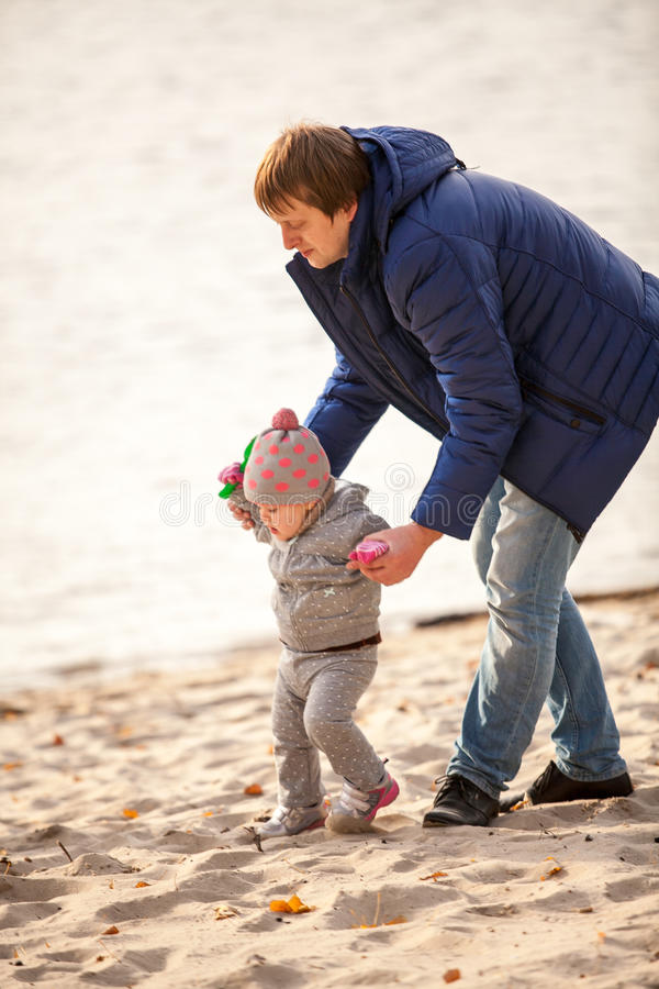 Vater, der mit kleiner Tochter auf Strand geht lizenzfreies stockfoto