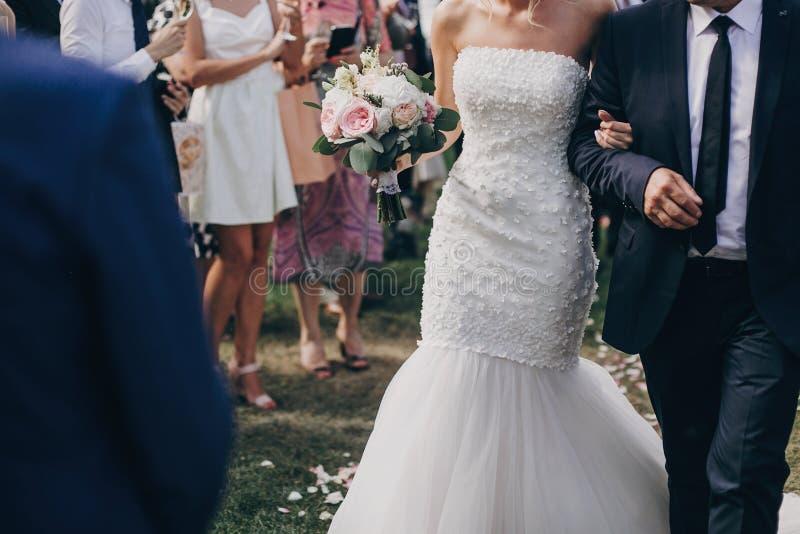 Vater, der mit Tochter, schöne stilvolle Braut, hinunter Heiratsgang mit den rosafarbenen Blumenblättern auf Gras unter Gästen ge lizenzfreies stockfoto