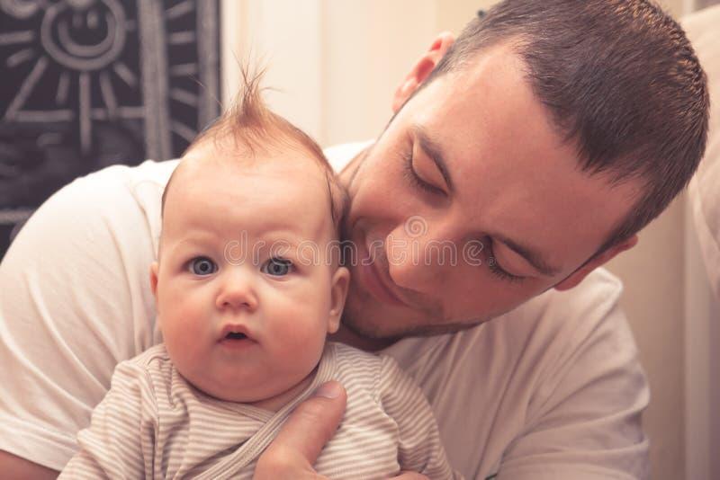 Vater, der sein kleines Baby umfasst Vater schaut auf Baby, Baby schaut auf Kamera Baby mit lustigem Haarschnitt lizenzfreie stockfotografie