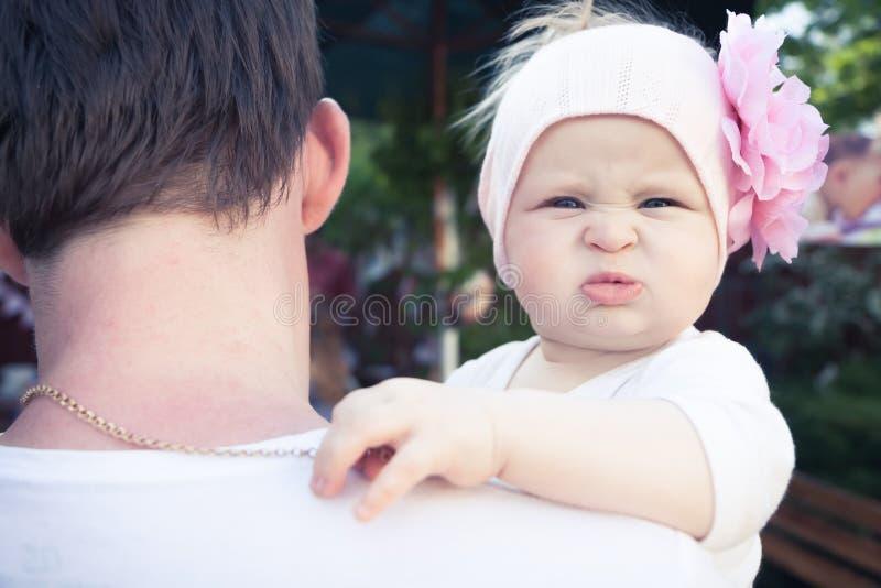 Vater, der sein nettes lustiges kleines Baby umfasst Vater schaut weg, schaut Baby mit lustigem Gesicht auf Kamera und umfasst se stockfoto