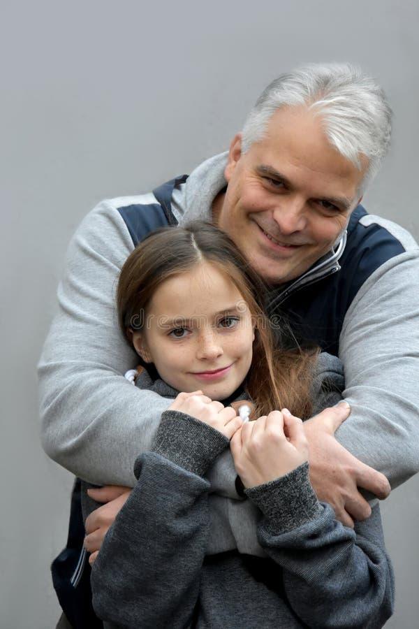 Vater, der seine jugendliche Tochter umarmt lizenzfreie stockfotografie