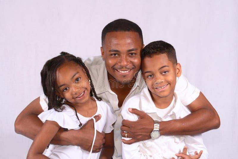 Vater, der seine Kinder huging ist stockfotografie