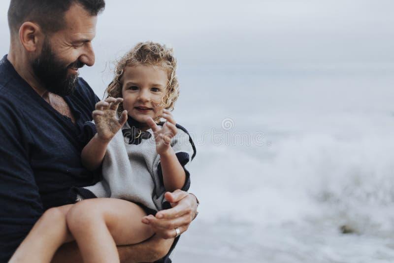 Vater, der seine Tochter durch das Meer hält stockfoto