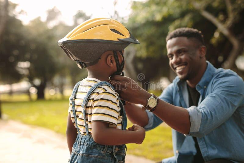 Vater, der seinem Sohn hilft, einen Radfahrensturzhelm zu tragen lizenzfreies stockfoto