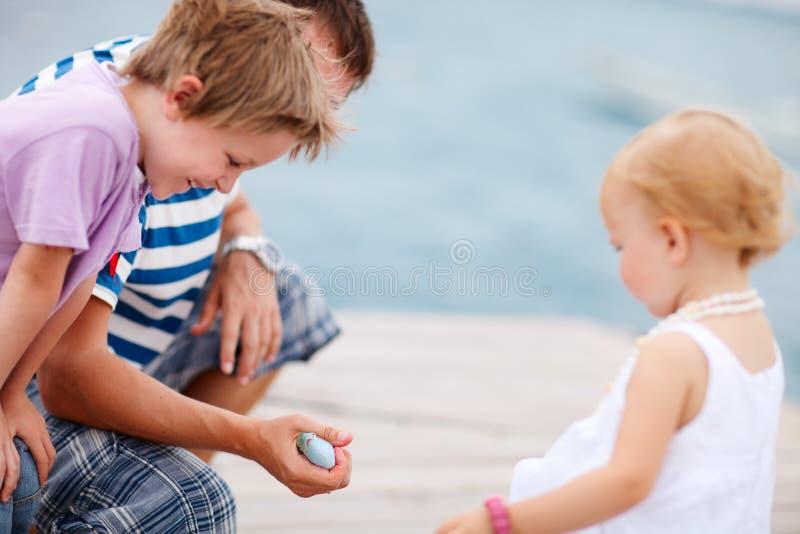 Vater, der seinen Kindern einen Fisch zeigt. stockbild
