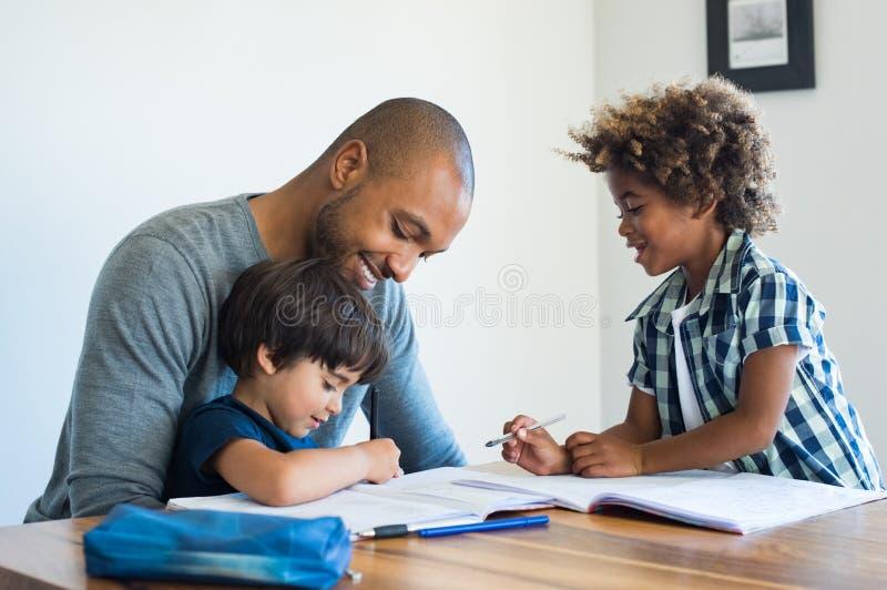 Vater, der seinen Söhnen mit Hausarbeit hilft stockfotos
