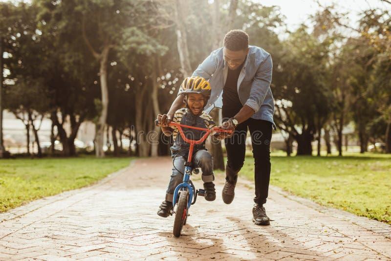 Vater, der seinen Sohn radfährt am Park unterrichtet stockbilder