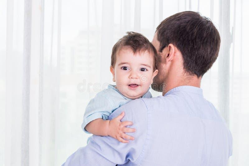 Vater, der seinen Sohn trägt Baby der guten Gesundheit, das auf Schulter von lächelt stockfoto
