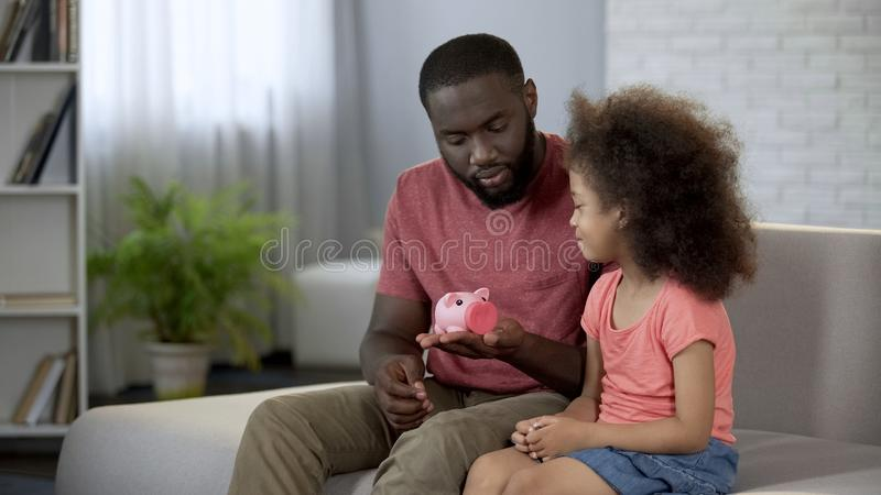 Vater, der weniger Tochter Sparschwein, unterrichtendes Kind gibt, um Geld zu sparen lizenzfreies stockfoto