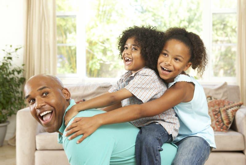 Vater, der zu Hause mit Kindern spielt lizenzfreie stockbilder