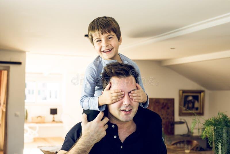 Vater, der zu Hause mit seinem Sohn auf seinen Schultern spielt Konzept des Glückes, der Liebe und der Freude zwischen einem Vati lizenzfreie stockfotografie