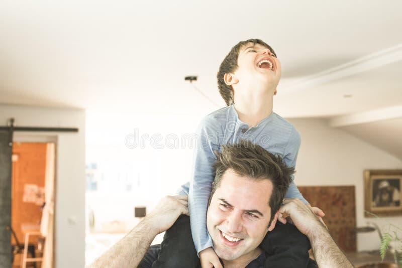 Vater, der zu Hause mit seinem Sohn auf seinen Schultern spielt Konzept des Glückes, der Liebe und der Freude zwischen einem Vati stockfoto
