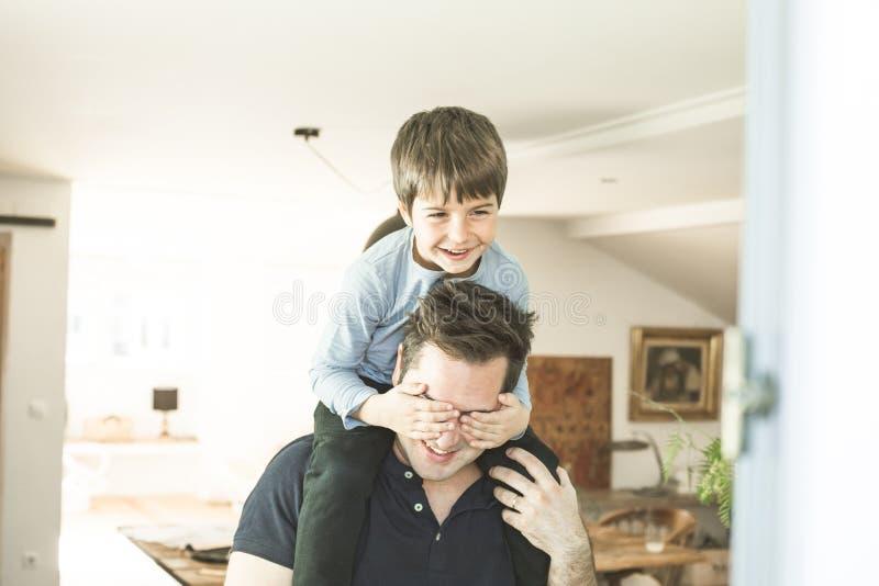 Vater, der zu Hause mit seinem Sohn auf seinen Schultern spielt Konzept des Glückes, der Liebe und der Freude zwischen einem Vati lizenzfreies stockbild