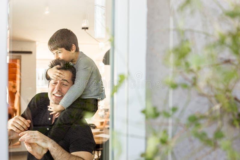 Vater, der zu Hause mit seinem Sohn auf seinen Schultern spielt Liebe und Glück zwischen Kind und Vater lizenzfreie stockfotos
