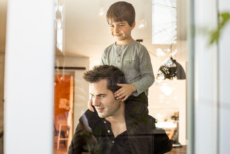 Vater, der zu Hause mit seinem Sohn auf seinen Schultern spielt Liebe und Glück zwischen Kind und Vater lizenzfreies stockbild
