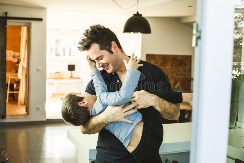 Vater, der zu Hause mit seinem Sohn auf seinen Schultern spielt Liebe und Glück zwischen Kind und Vater lizenzfreie stockfotografie
