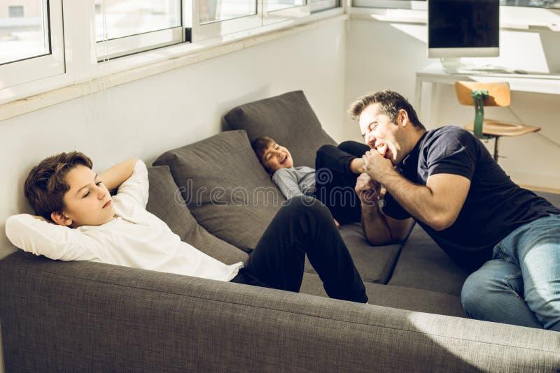 Vater, der zu Hause mit seinen Kindern auf der Couch spielt stockfoto